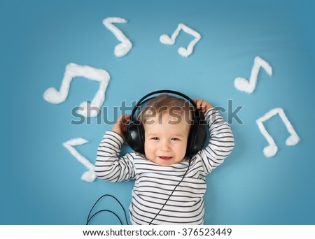 little boy on blue blanket background with headphones - stock photo