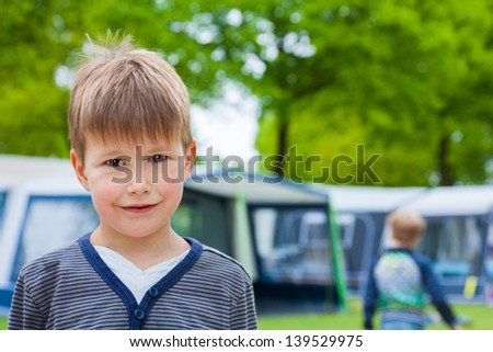 Little boy on camping site with caravan tent in background - stock photo