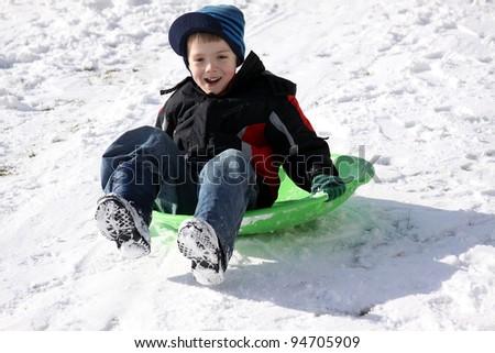 Little boy on his sled, enjoying winter - stock photo