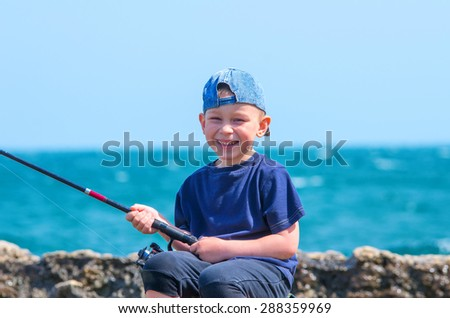 Little boy on sea fishing, holding a fishing rod and smiles. Family composition