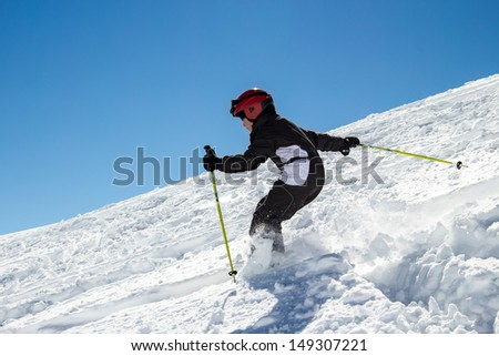 Little boy on skis in deep snow on a steep slope