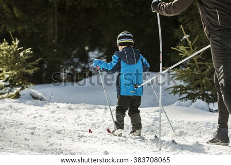 Little boy on skis on a running track in the woods. He pushed a running wand - stock photo