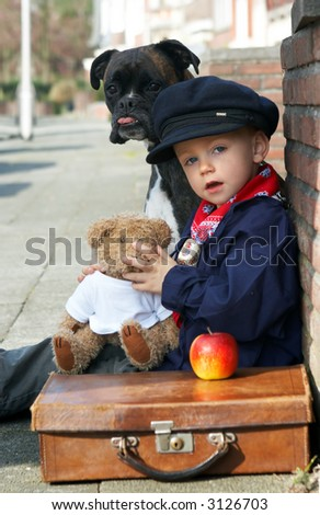 Little boy on the road with his dog and teddy bear - stock photo