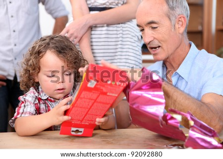 Little boy opening a gift from his grandfather - stock photo
