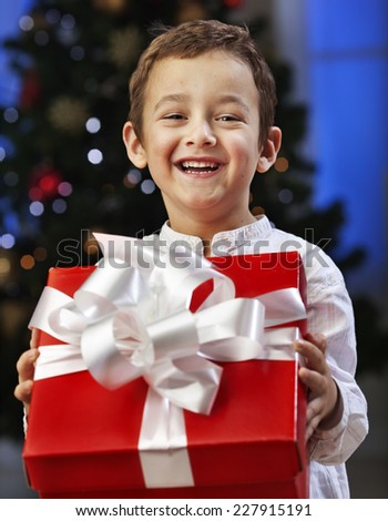 Little boy opening Christmas present and smiling - stock photo