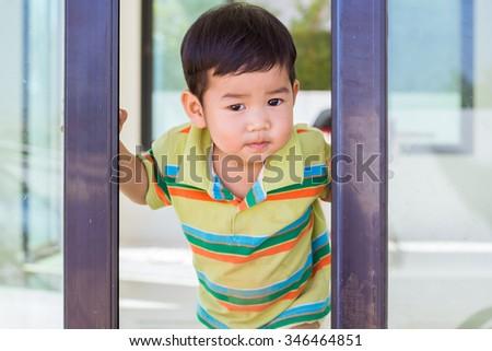 Little boy opening door in the house - stock photo