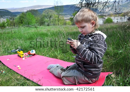 little boy outdoors does not want to play toys, he wants mobile phone - stock photo