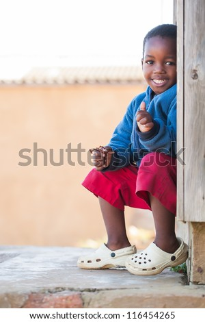 Little boy outside on the porch of his home. - stock photo