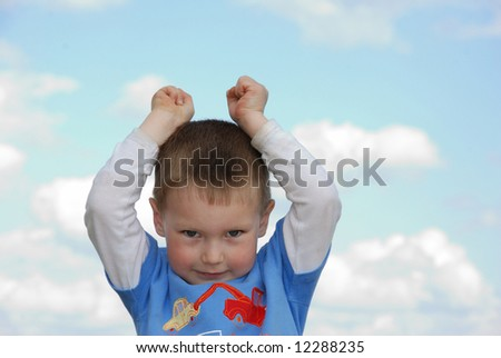 Little boy over cloudy blue sky with hands on his head - stock photo