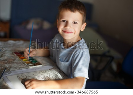 Little boy painting at home by watercolor coloring book - stock photo
