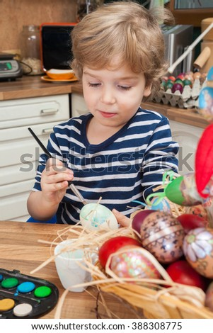 Little boy painting Easter eggs with paintbrush at home. Small boy coloring Easter eggs. - stock photo