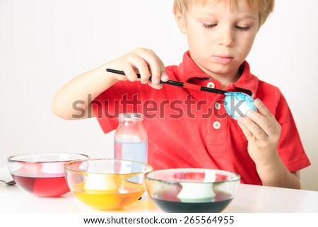 little boy painting eggs for easter holiday - stock photo