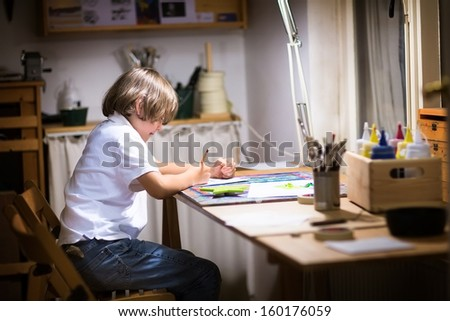Little boy painting in a dark room late in the evening
