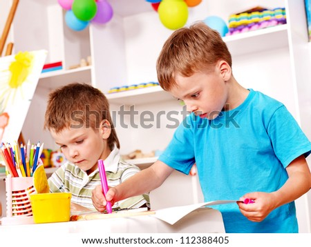 Little boy painting  in kindergarten. - stock photo