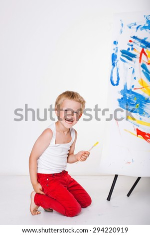 Little boy painting on canvas. Education. Creativity. Studio portrait over white background - stock photo