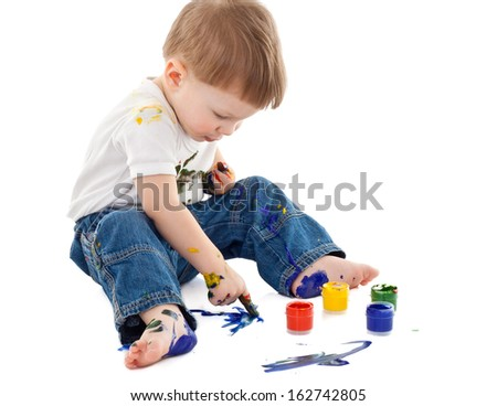 little boy painting on the floor and stained in paint on white background  - stock photo