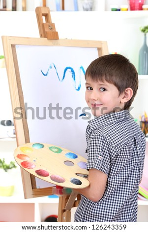Little boy painting paints picture on easel - stock photo