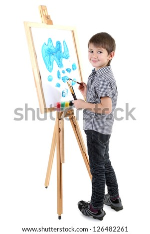 Little boy painting paints picture on easel isolated on white - stock photo