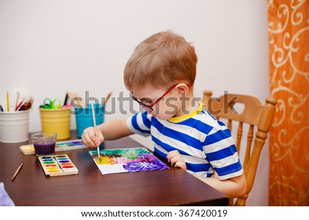 Little boy painting with brush and watercolors. - stock photo