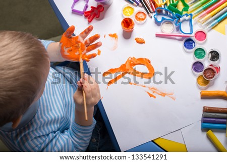Little boy painting with gouache on hand, top view - stock photo