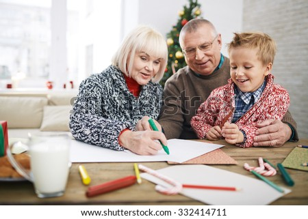 Little boy painting with grandpa and grandma - stock photo