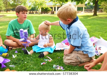 Little boy pats a birthday girl's head - stock photo
