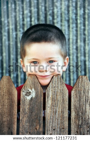 Little boy peeks over his backyard fence.  He is resting his head on the wooden slats and is lost in thought. - stock photo