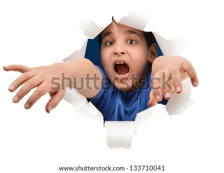 Little boy peeps through a hole torn in the paper  looking out of a hole - stock photo
