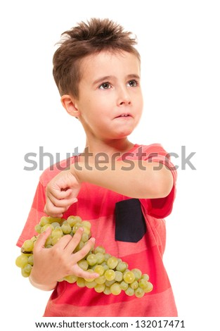 Little boy picks up the berry from bunch of grapes isolated on white - stock photo