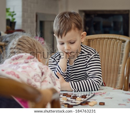 Little boy planning his strategy staring thoughtfully at the board as he sits at a table playing a game of checkers or draughts with his sister - stock photo