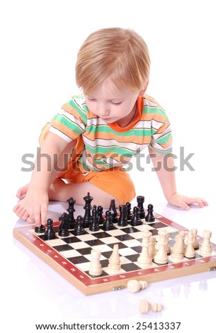 Little boy play chess on the ground.