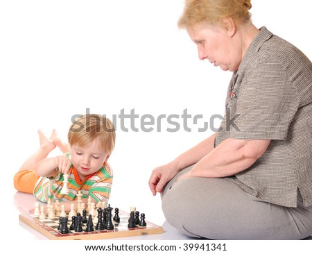 Little boy play chess with his grandmother on the floor. - stock photo