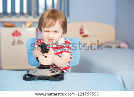 Little boy play computer games in his room with joystick - stock photo