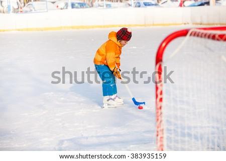 Little boy play ice hockey outside - stock photo