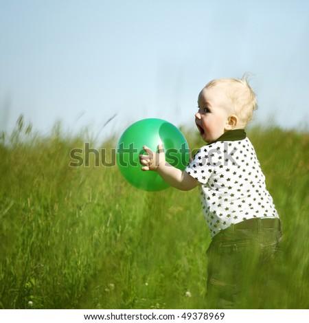 little boy play in green grass - stock photo