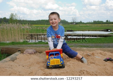 Little boy play in the sand box with color toy car