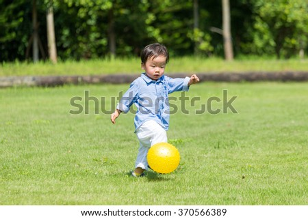 Little boy play soccer at park - stock photo
