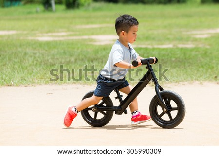 Little boy play with bicycle - stock photo