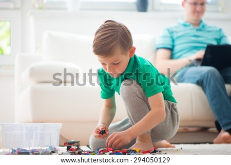 Little boy play with building kit, father works with laptop - stock photo