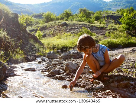 little boy play with flowing water in mountain, summer nature outdoor