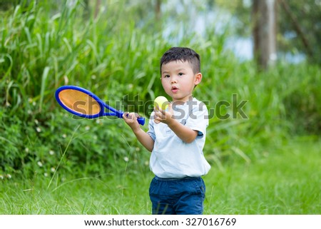 Little boy play with tennis at park - stock photo