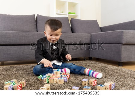 Little boy play wooden toy block at home - stock photo