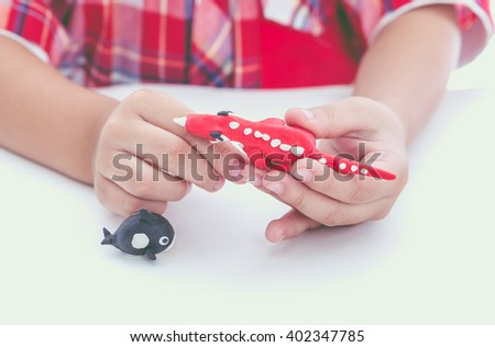 Little boy playing and creating toys from play dough. Child molding model clay. Strengthen the imagination of child. Vintage style. Cross process. - stock photo