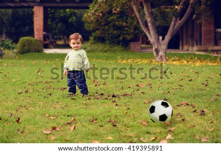 Little boy playing at the garden with a soccer ball