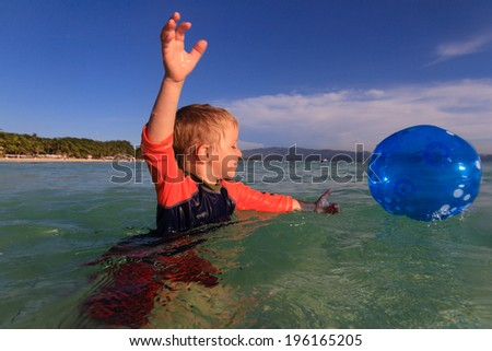little boy playing ball in water - stock photo