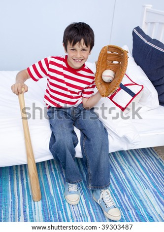 Little boy playing baseball in his bedroom - stock photo