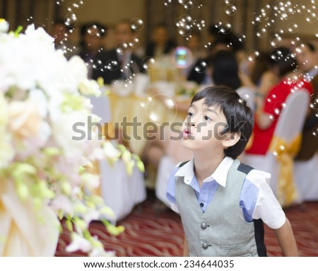 Little boy playing bubbles in the party indoor - stock photo