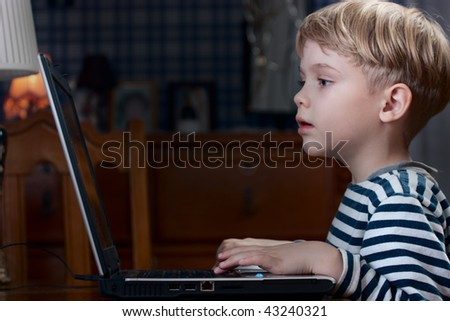 little boy playing computer game on laptop very emotional - stock photo