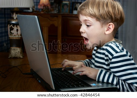 little boy playing computer game very emotional - stock photo