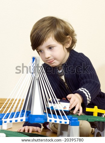 little boy playing concentrated with his train set. Shallow DOF. - stock photo